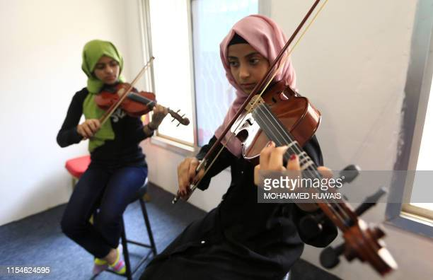 Yemeni girls play the violin at the Yemeni House of Music and Arts in the capital Sanaa on July 3 2019 The centre which has hundreds of students is a...