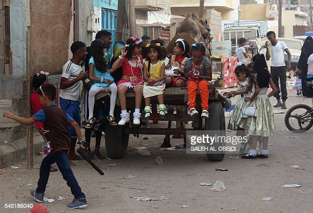 Yemeni girls sit on the back of a cameldrawn cart as people gather in the street during celebrations for Eid alFitr which marks the end of the Muslim...