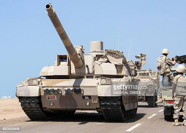 Yemeni government forces' tanks and armoured vehicles watch as tanks pass on the road leading to the southwestern port of Mokha after they recaptured...