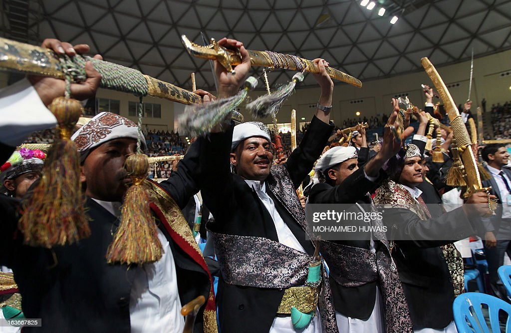 Yemeni grooms dance as they take part in a mass wedding