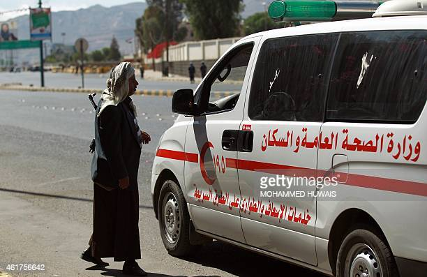 Yemeni gunman stands next to an ambulance parked in the area neat the presidential palace in Sanaa on January 19, 2015 during fierce clashes between...