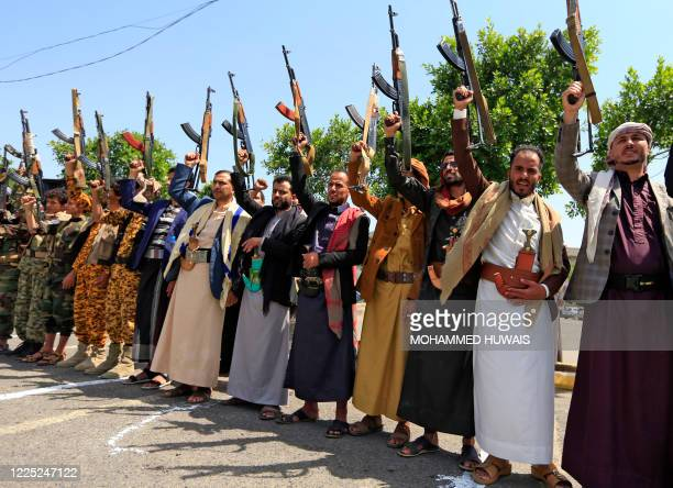 Yemeni gunmen loyal to the Huthi movement brandish their weapons during a rally in the capital Sanaa to show support to the movement against the...