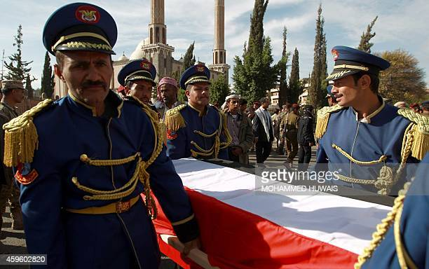 Yemeni honor guards carry coffins of the victims of recent attacks by alQaeda militants during a funeral procession on November 26 2014 in the Yemeni...