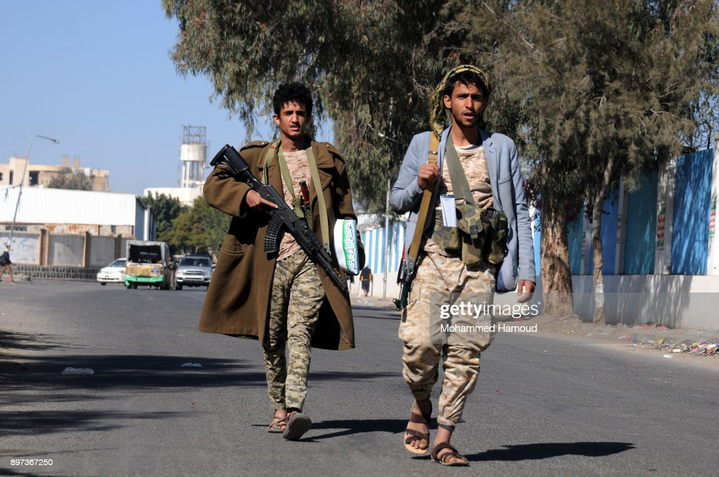 Yemeni Houthi members walk after they attended a tribal gathering