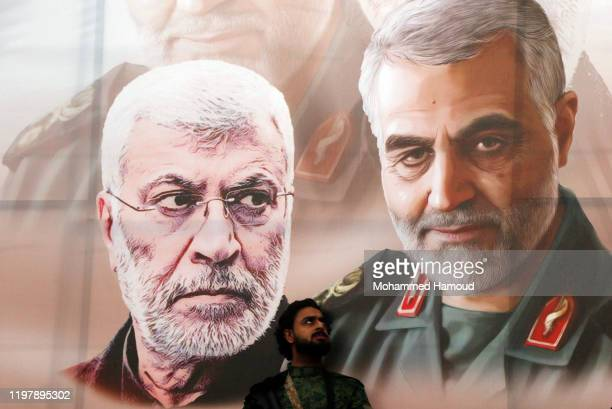 Yemeni Houthi-supporter stands by a banner shows pictures of the Iranian commanders Qassem Soleimani and Abu Mahdi al-Muhandis, who were killed by...