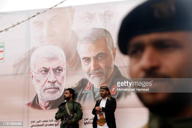 Yemeni Houthi-supporters stand by a banner shows pictures of the Iranian commanders Qassem Soleimani and Abu Mahdi al-Muhandis, who were killed by...