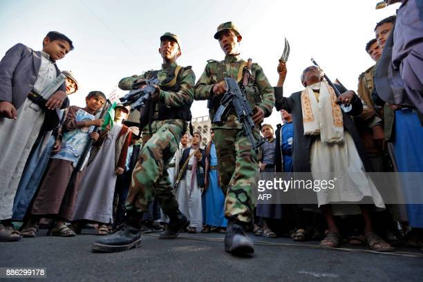 TOPSHOT Yemeni Huthi rebel fighters march during a rally celebrating the death of Yemeni expresident Ali Abdullah Saleh a day after he was killed in...
