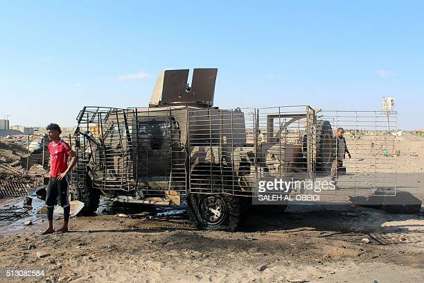 A Yemeni inspects a burnt armored vehicle after a suicide bomber rammed his explosivesladen vehicle into an area where security forces and...