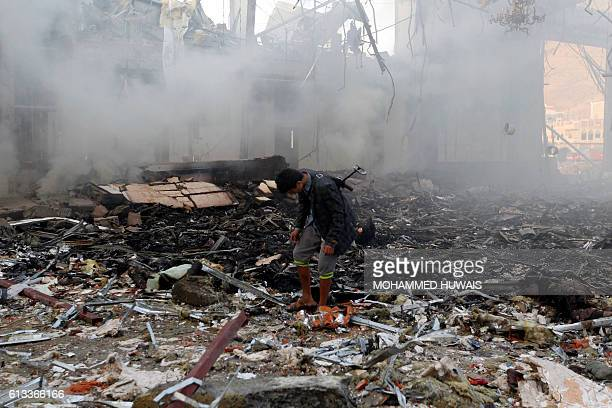 A Yemeni inspects the rubble of a destroyed building following an air strike on a funeral ceremony in the capital Sanaa on October 8 2016 Rebels in...