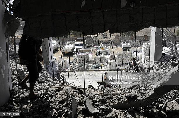 Yemeni inspects the wreckage of a building after the war crafts belonging to the Saudiled coalition carried out airstrikes in Sanaa Yemen on February...