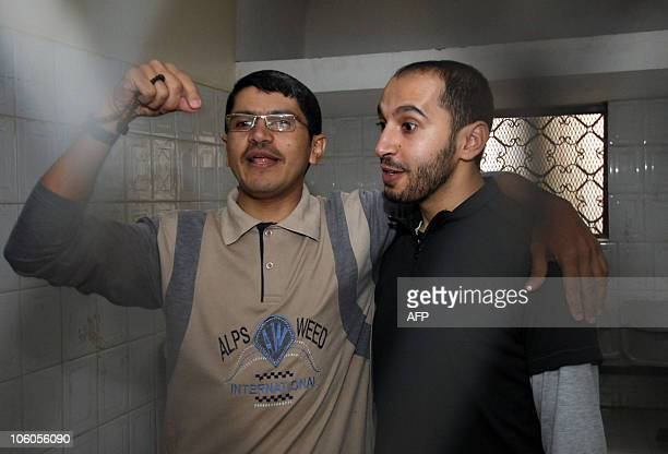 Yemeni journalist Abdul Ilah Haider Shaea and his assistant Abdul Karim Daoud alShami stand behind bars at the start of their trial on the charges of...