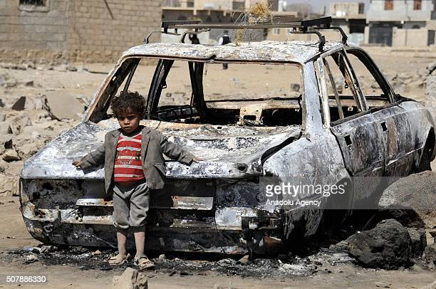 Yemeni kid leans on a wreckage of car after the war crafts belonging to the Saudiled coalition carried out airstrikes in Sanaa Yemen on February 01...