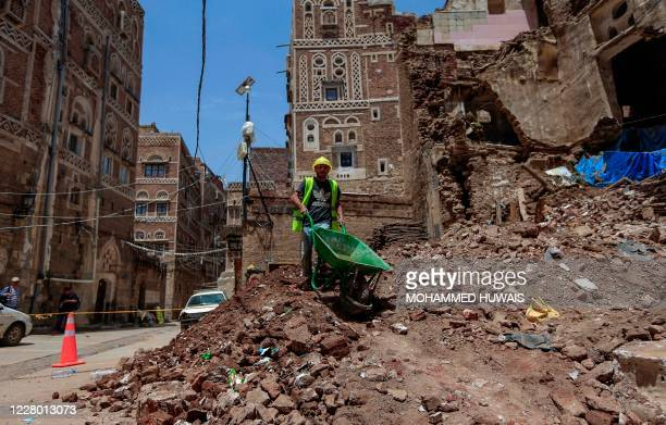 Yemeni labourer removes the rubble ahead of restoration works on the site of a collapsed UNESCO-listed building following heavy rains, in the old...
