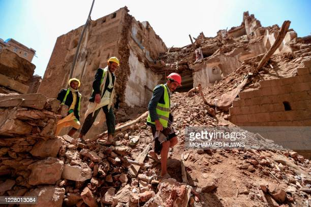 Yemeni labourers arrive to remove the rubble ahead of restoration works on the site of a collapsed UNESCO-listed building following heavy rains, in...