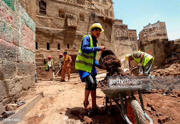 Yemeni labourers remove the rubble ahead of restoration works on the site of a collapsed UNESCO-listed building following heavy rains, in the old...