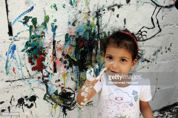 Yemeni little girl shows her paintbrush as she participates in an Open Day of graffiti campaign call for peace on March 15, 2018 in Sana'a, Yemen.