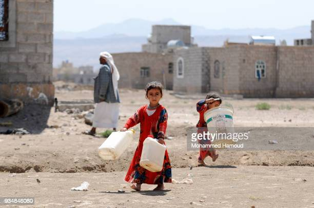 Yemeni little sisters carry jerrycans as they walk to a water pump to fill it with water on March 18 2018 in Sana'a Yemen