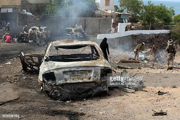 Yemeni loyalist forces and onlookers gather at the scene of a suicide attack targeting the police chief in the base of the Saudibacked government on...