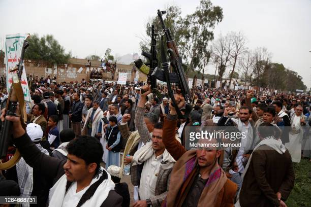 Yemeni loyalists of the Shi'ite Houthi movement hold their hands as they shout slogans during a rally held for celebrating the anniversary of Eid...