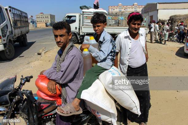 A Yemeni man and child ride on a motorcycle loaded with sacks of wheat and cooking oil containers distributed as food aid by a local charity at a...