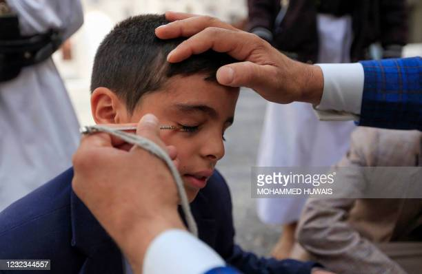 Yemeni man applies traditional Kohl eyeliner to a youth's eyelid at the Mosque of Sanaa during the Muslim fasting month of Ramadan, on April 16, 2021.