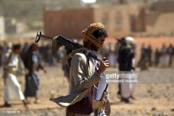 Yemeni man carries a Kalashnikov rifle as he takes part in a gathering near the capital Sanaa to show support to the Shiite Huthi movement against...