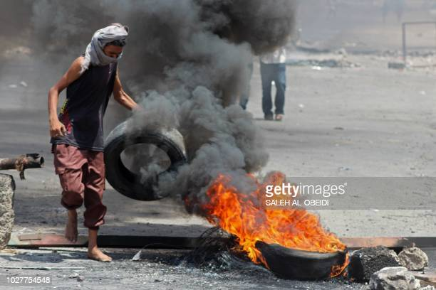 A Yemeni man carries a tyre into a fire in Crater on September 6 as protesters demonstrate against inflation and the rise of living costs near the...