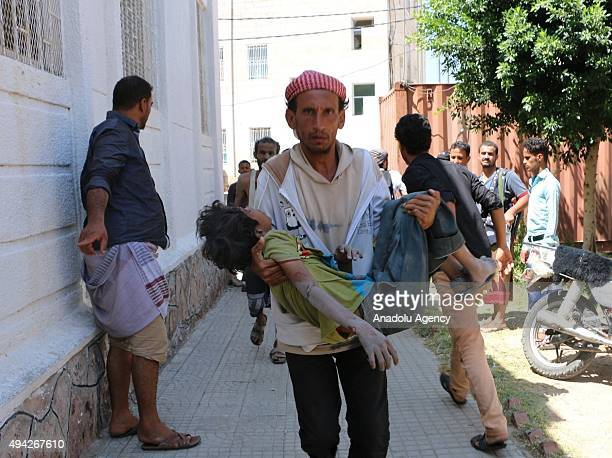 Yemeni man carries an injured child after Saudiled coalition airstrikes targeting Houthicontrolled areas in Taiz's Su'bat region on October 25 2015