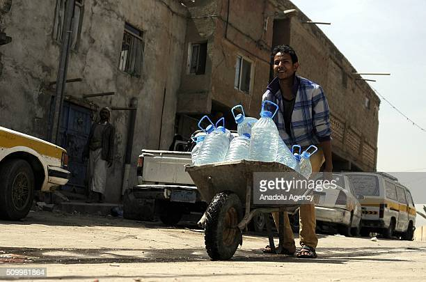 Yemeni man carries plastic bottles to fill them with water in Shwaob neighborhood as the political crisis in the country continues in Sana'a Yemen on...