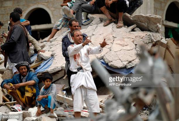 A Yemeni man covered in blood stains reacts as they search for survivors in the debris of buildings hit in an air strike in the residential southern...