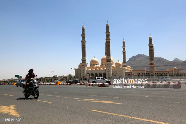 A Yemeni man drive his motorcycle in front of the Saleh mosque named recently by Houthis as 'alSha'ab' on August 20 2019 in Sana'a Yemen