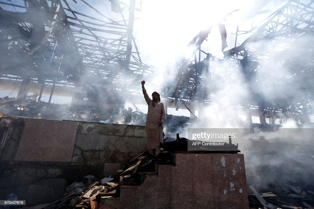 Yemeni man gestures at the site of an air strike in the capital Sanaa, on November 5, 2017. Yemen's rebel-held capital was struck by overnight air raids that continued well into the next day, targeting the defence ministry and a popular public square, an official said. /