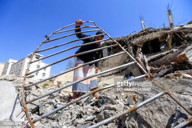 A Yemeni man goes through the wreckage of a building that was reportedly destroyed in a Saudiled coalition air strike in the capital Sanaa on...