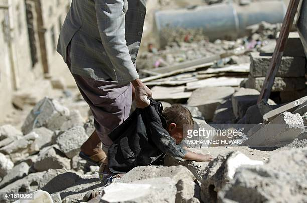 A Yemeni man grabs a child by his clothes as he searches for survivors under the rubble in houses destroyed by an overnight Saudiled air strike on a...