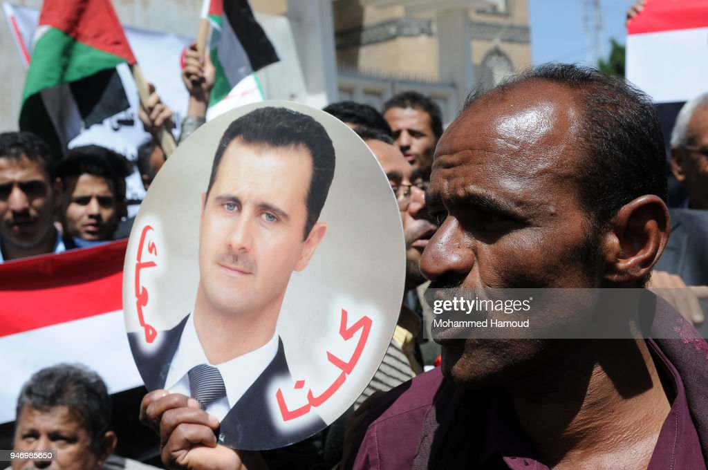 A Yemeni man holds a photo of Syrian President Bashar al-Assad during a protest against U.S. allied missile strikes against Syria outside the Syrian embassy on April 16, 2018 in Sana'a, Yemen. The U.S., Great Britain and France launched missile strikes in response to the Syrian goverment using chemical weapons against its own population.