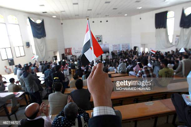A Yemeni man holds up the national flag during celebrations marking the third anniversary of the Yemeni revolution that toppled former president Ali...