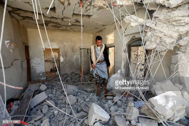 Yemeni man inspects the damage in the aftermath of a reported air strike by the Saudiled coalition in the Yemeni capital Sanaa on March 8 2018 / AFP...