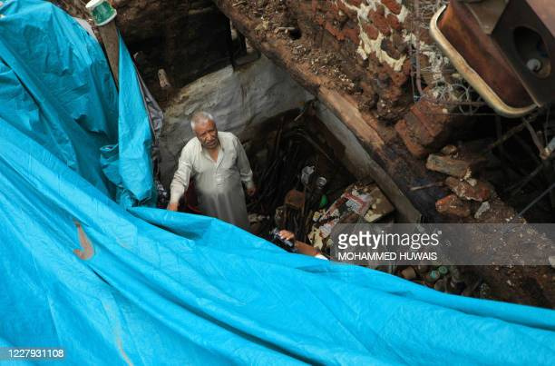 Yemeni man inspects the ruins of a building which collapsed following heavy rain fall on August 5, 2020 in the old city of the Yemeni capital Sanaa....