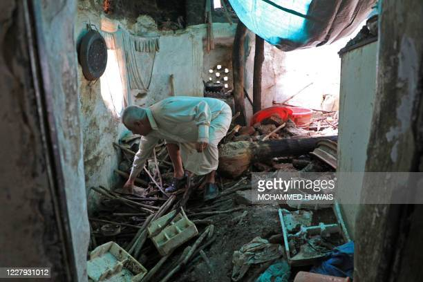 Yemeni man inspects the the damages in a building which partially collapsed following heavy rain fall on August 5, 2020 in the old city of the Yemeni...