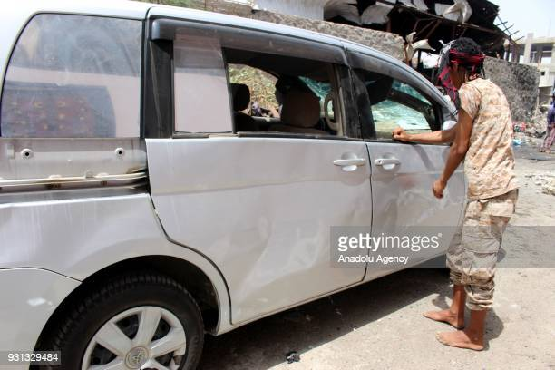 Yemeni man inspects wreckages of a car after a boobytrapped car hit a mess hall serving Yemeni forces trained by the United Arab Emirates in Sheikh...
