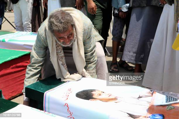 A Yemeni man mourns over a casket on August 13 2018 during a mass funeral in the northern Yemeni city of Saada a stronghold of the Iranbacked Huthi...