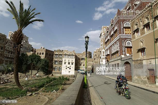 A Yemeni man ride his motorcycle past historic buildings in the historical quarter in the Yemeni capital Sanaa currently listed as one of the world...