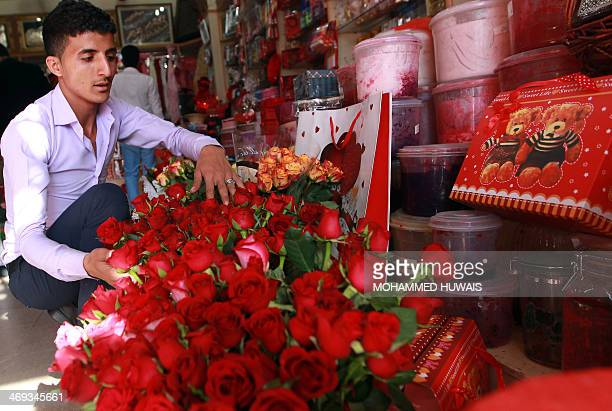 A Yemeni man selects flowers to buy at a shop in the Yemeni capital Sanaa on February 14 2014 AFP PHOTO/ MOHAMMED HUWAIS