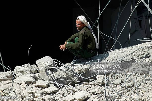 A Yemeni man sits amidst the rubble of the police headquarters after the building was struck overnight by Saudiled air strikes on January 18 2016 in...