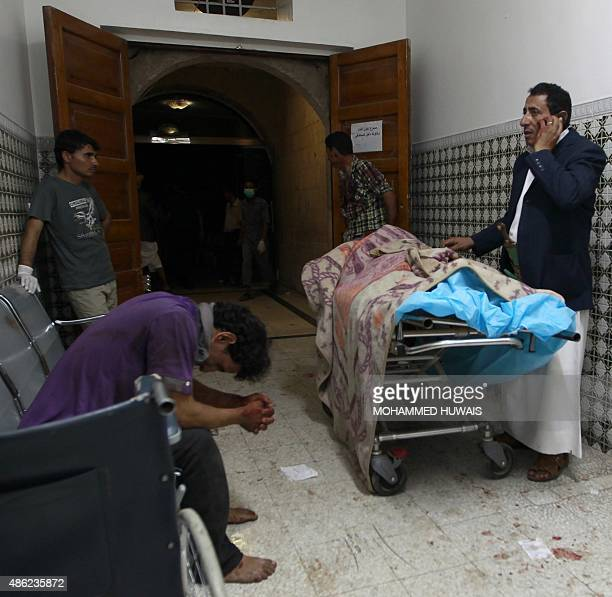 A Yemeni man talks on the phone as others react next to a body on a gurney at a hospital in Sanaa as injured victims arrive following a twin suicide...