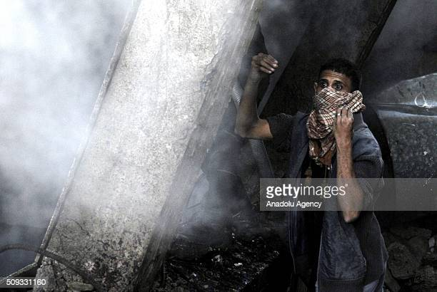 Yemeni man tries to extinguish fire after the war crafts belonging to the Saudiled coalition carried out airstrikes at Beit alMiad district of Sanaa...