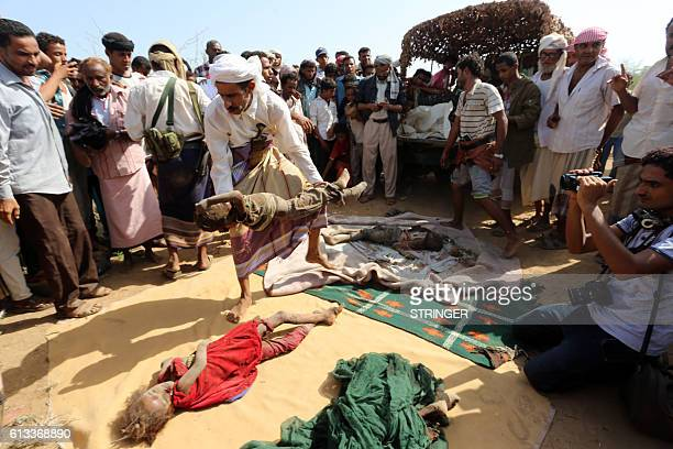 A Yemeni man unloads the bodies of children on October 8 during the funeral of members of the same family a day after they were killed in a reported...