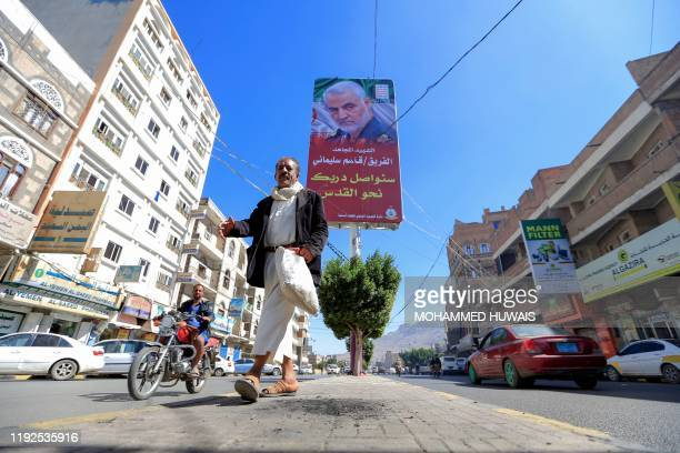 A Yemeni man walks beneath a poster of slain Iranian military commander Qasem Soleimani in the capital Sanaa on January 8 2020 Soleimani and and...