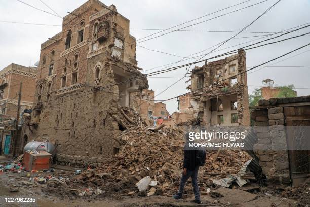 Yemeni man walks by a collapsed UNESCO-listed building in the old city of the Yemeni capital Sanaa following heavy rains, on August 8, 2020.