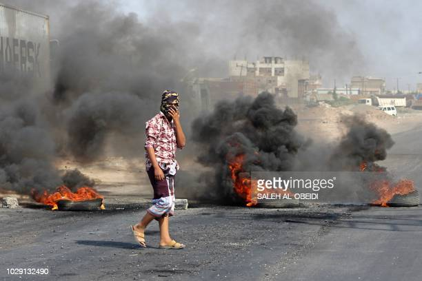 A Yemeni man walks by burning tyres as protesters demonstrate against inflation and the rise of living costs in the country's second city of Aden on...